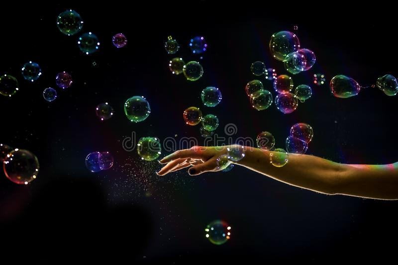 The transparent, iridescent soap bubbles isolated on black. stock photography