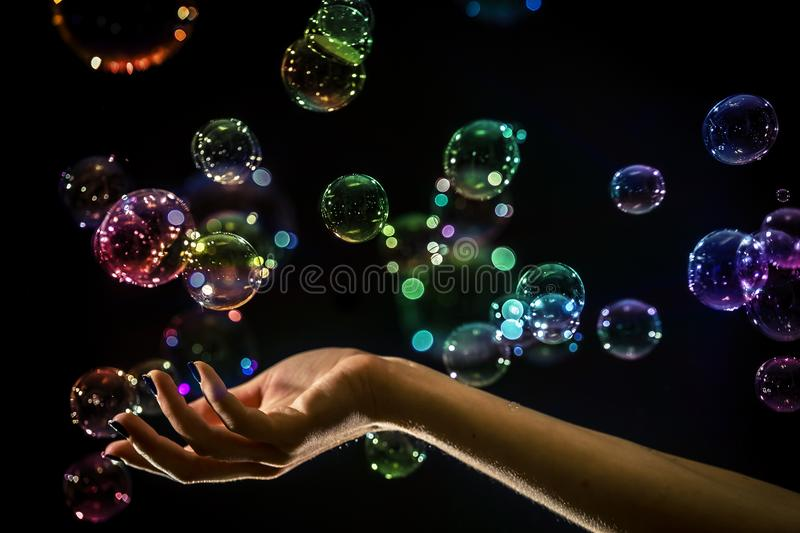 The transparent, iridescent soap bubbles isolated on black. royalty free stock images