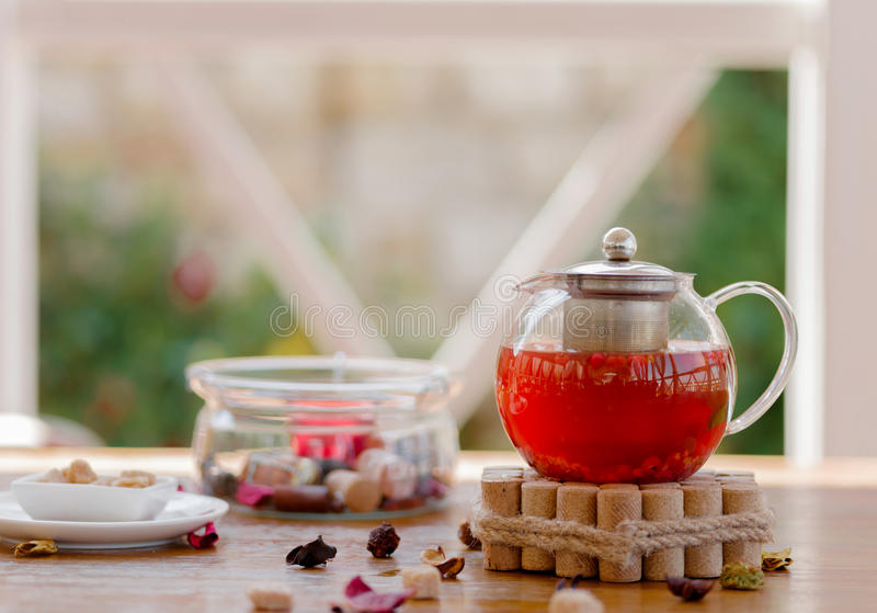 A transparent kettle full of fruity drink and a box of sugar cubes on a wooden table. Tea composition in the outdoors. stock photography