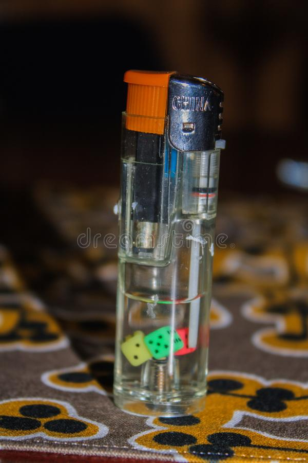 Transparent lighter on a thematic table. Nice lighter with a pair of coloured dices inside on the top of a thematic table stock photo