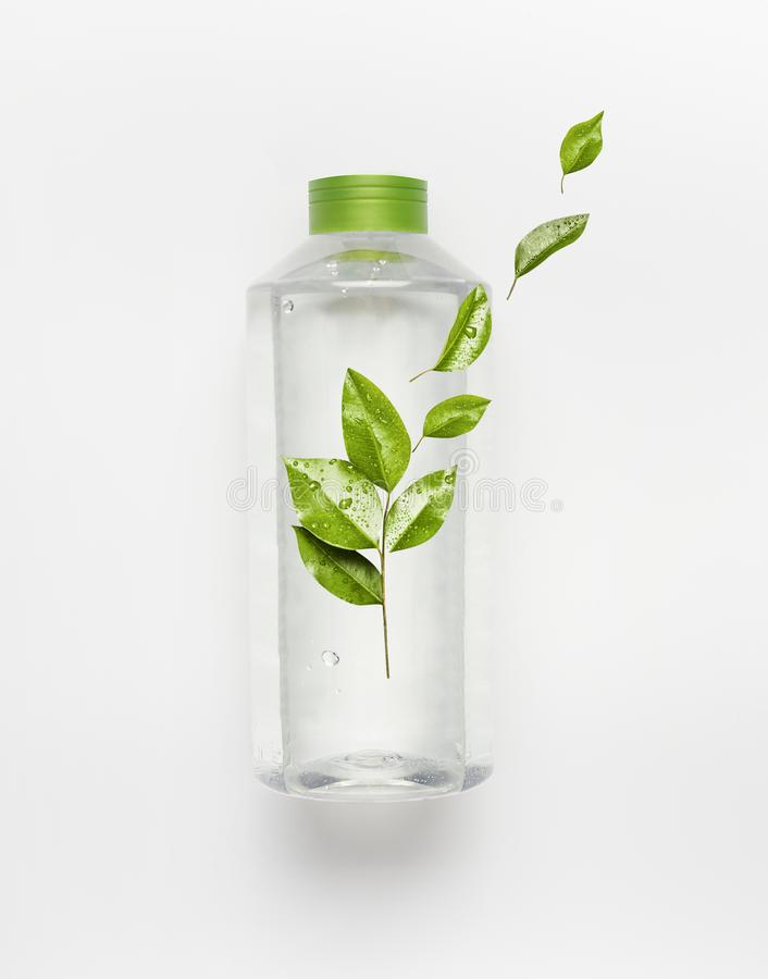 Transparent liquid bottle with green lid. Clear nature water with green flying leaves and branding mock up royalty free stock image