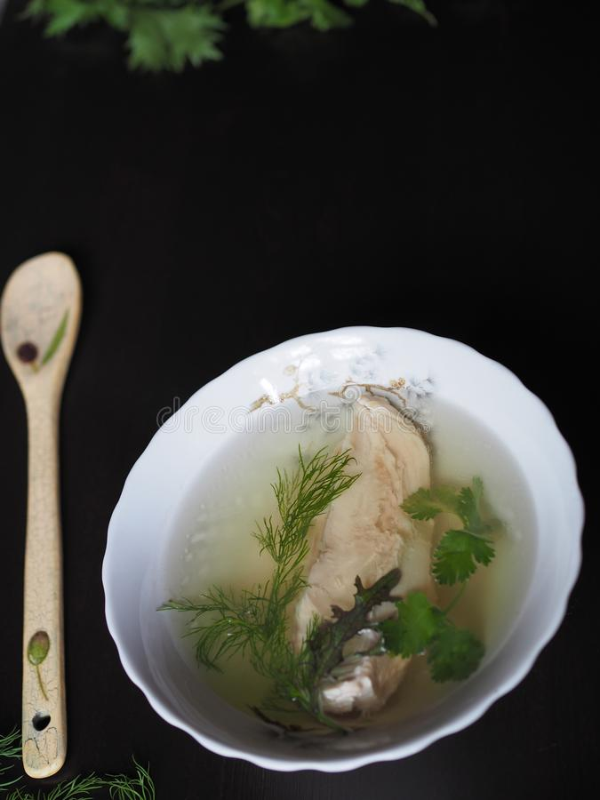 Chicken soup with herbs in a white plate on a dark background. royalty free stock photography