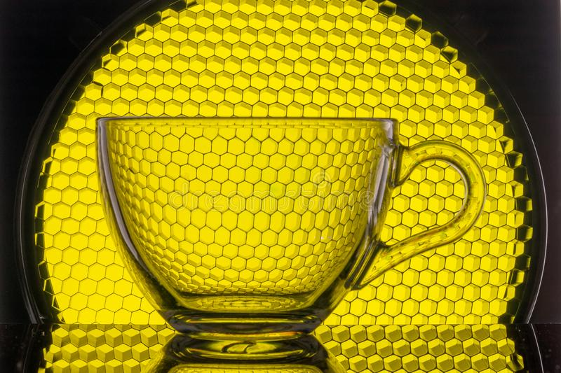 transparent mug on a background of yellow honeycomb for photography stock image