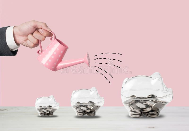 Transparent piggy bank filled with coins on wood background.Saving investment colorful concept.Watering can and money growth draw royalty free stock photography