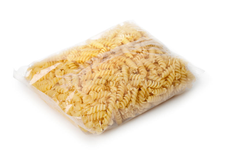 Transparent plastic bag of fusilli pasta. On white royalty free stock image