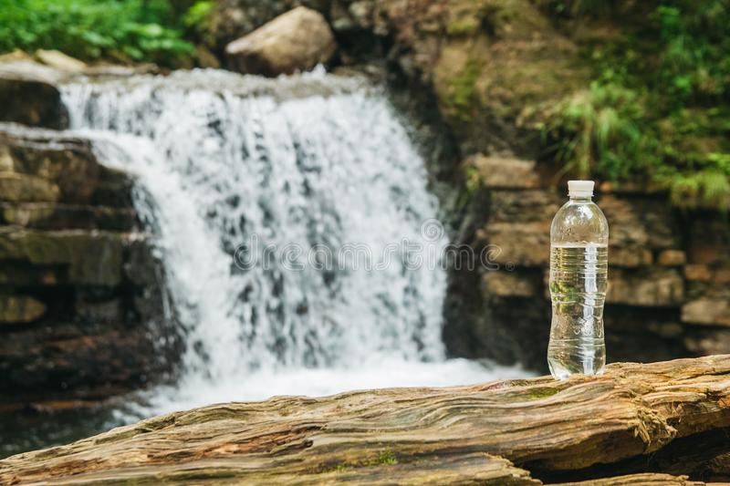 Transparent plastic bottle with water stands on a wooden trunk against the background of the river and the waterfall. The concept of pure natural drinking royalty free stock image