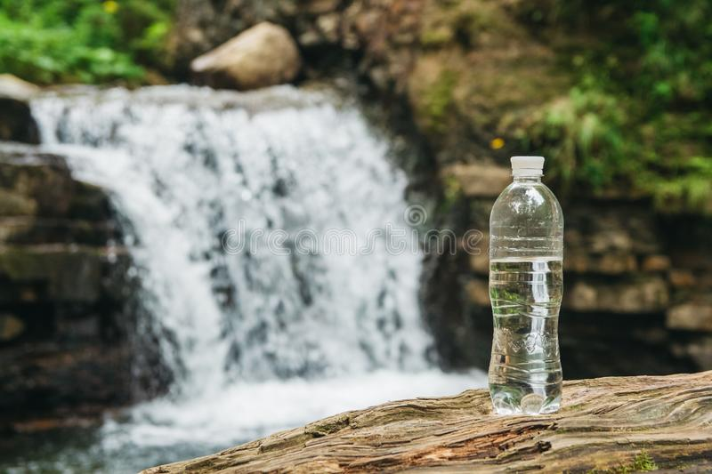 Transparent plastic bottle with water stands on a wooden trunk against the background of the river and the waterfall. The concept of pure natural drinking stock image