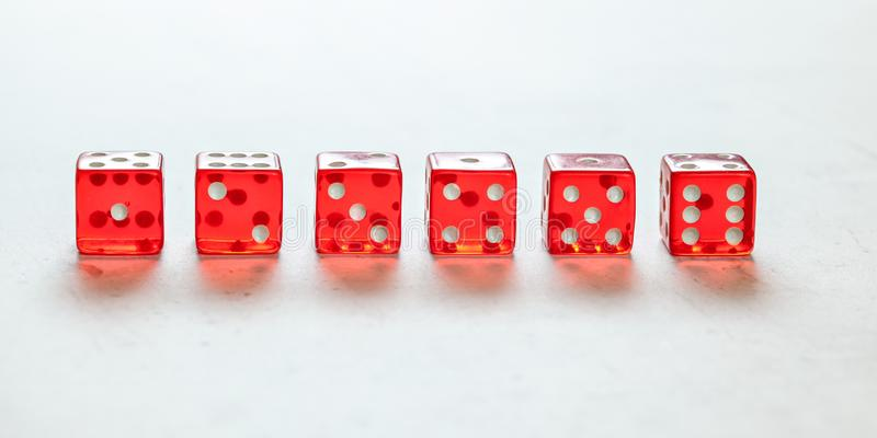 Transparent red craps dices arranged on white board, showing all numbers from one to six. Front view royalty free stock images