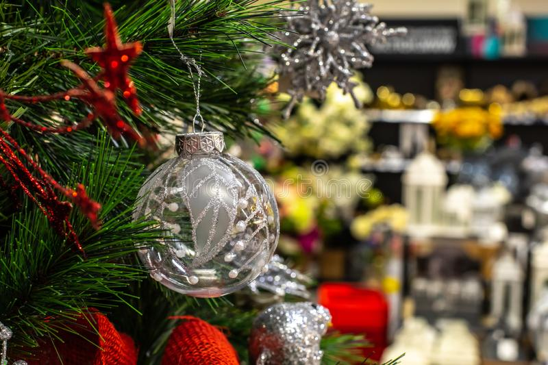 Transparent silver shiny ball on the Christmas tree against the background of defocus shelves in the store. Concept Christmas. Transparent silver shiny ball on royalty free stock photography