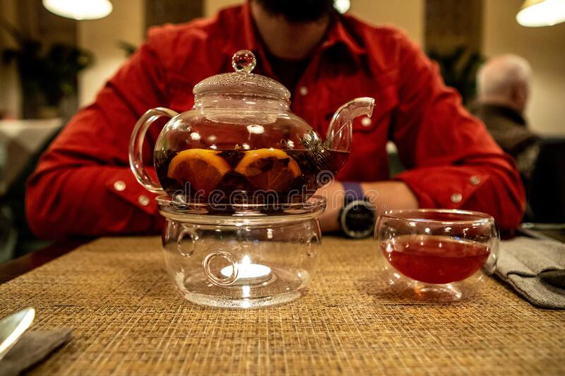 A transparent teapot with fruit tea stands on a table in a cafe in front of a defocused man in a red shirt royalty free stock photo