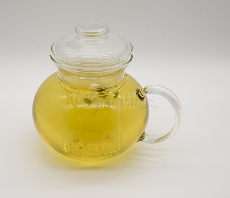 Transparent teapot with light fragrant chamomile tea stock image