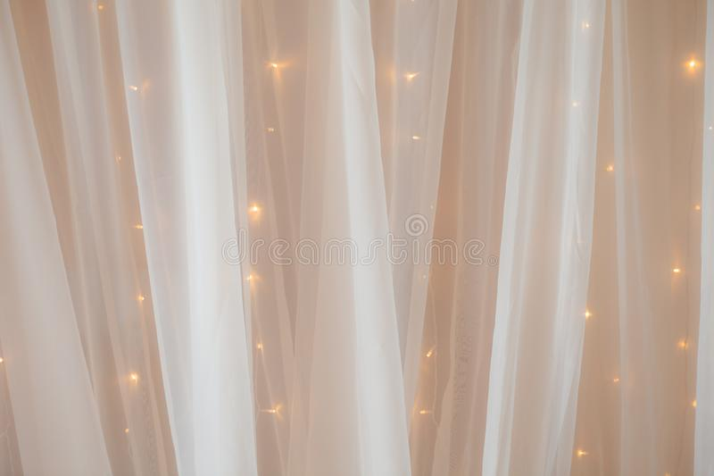 Transparent tulle with lights at the wedding ceremony, a place for photographing the groom, bride or guests royalty free stock photography