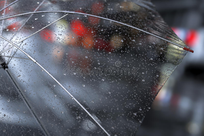 Transparent umbrella with rainy drops close up on street city lights background. stock illustration
