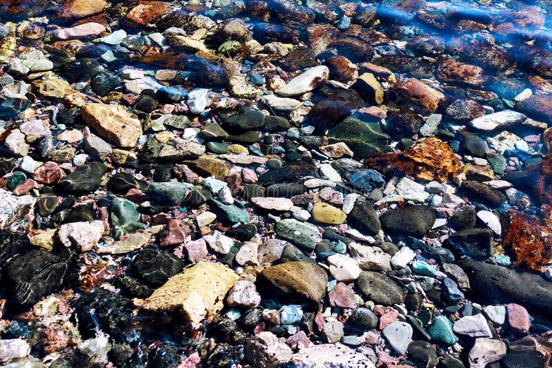 Transparent water sea texture with stones royalty free stock photos