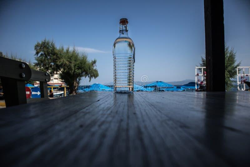 Transparente Flasche mit Wasser- und Himmelhintergrund stockfoto