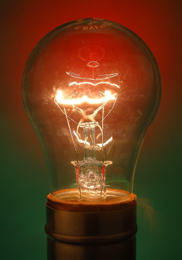 Transparente Glühlampe belichtet auf rotem und grünem Hintergrund lizenzfreie stockfotografie