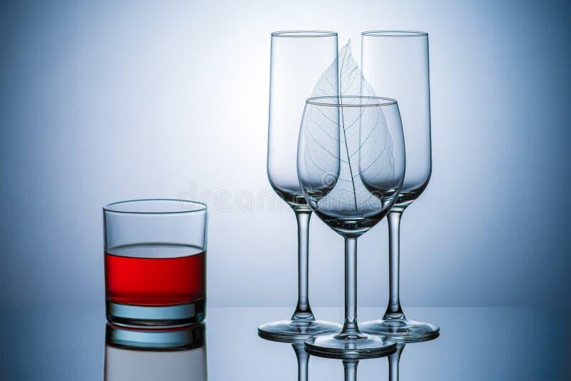 Transparente Glasbecher, Rum, Wein, blauer Hintergrund lizenzfreie stockbilder