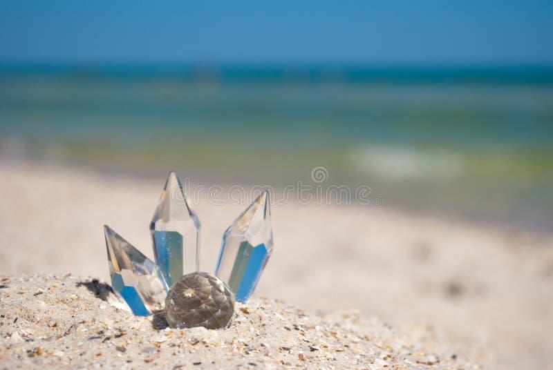 Transparente Glaskristalle auf dem Sand auf einem Hintergrund von blauem Meer und von blauem Himmel stockfoto