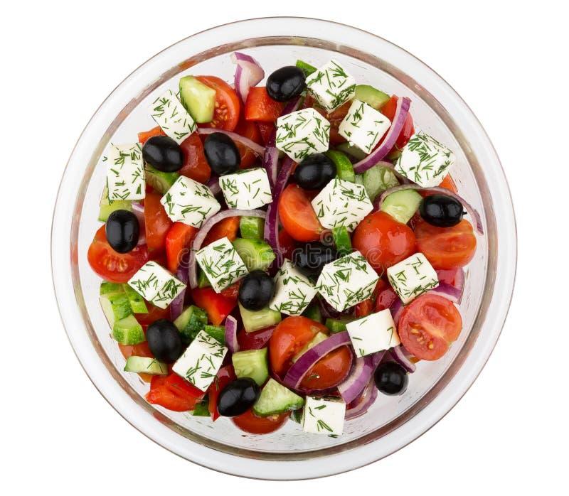 Transparente Glasschüssel mit dem griechischen Salat lokalisiert auf Weiß stockbild