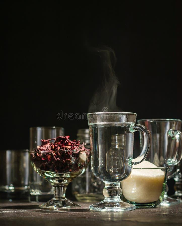 Transparente Glasschale mit heißem rotem Tee vom Hibiscus oder vom Hibiscus Glaswaren und trockene Blumenblätter mit Zucker stockbild