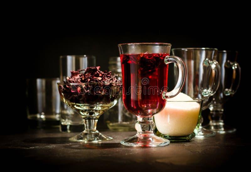 Transparente Glasschale mit heißem rotem Tee vom Hibiscus oder vom Hibiscus Glaswaren und trockene Blumenblätter mit Zucker stockfotos