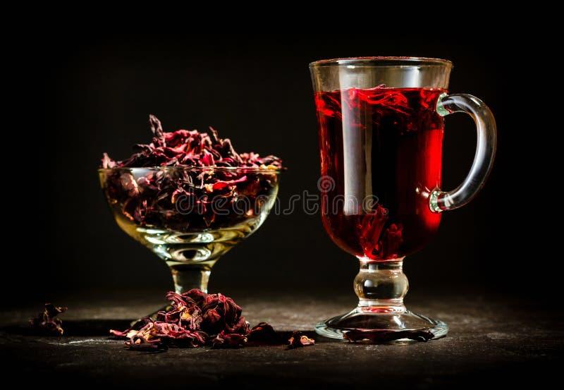 Transparente Glasschale mit heißem rotem Tee vom Hibiscus oder vom Hibiscus Glaswaren und trockene Blumenblätter mit Zucker lizenzfreie stockfotos