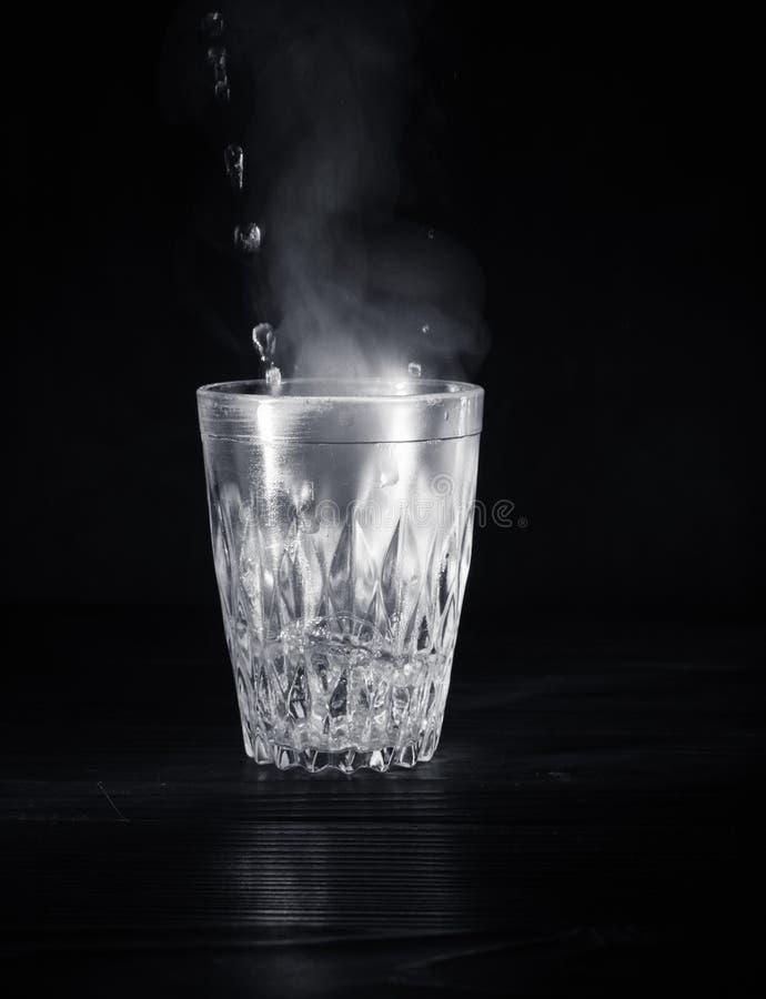 Transparente Glasschale mit Schwellen das kochende Wasser in es Der Dampf von der Spitze Schwarzer Hintergrund lizenzfreie stockfotos