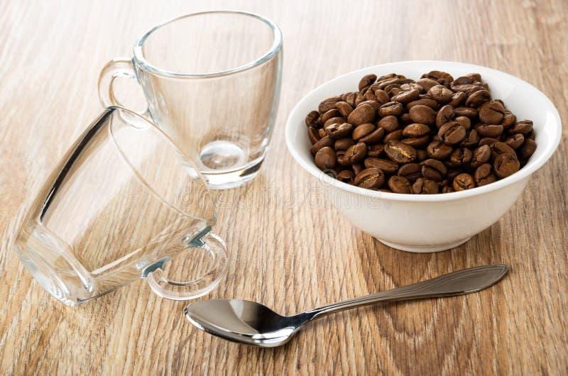 Transparente Glasschalen, Löffel und Schüssel mit Röstkaffeebohnen auf Tabelle lizenzfreies stockfoto