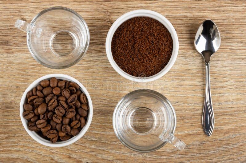 Transparente Schalen, L?ffel, Sch?ssel mit Kaffeebohnen, Sch?ssel mit gemahlenem Kaffee auf Tabelle Beschneidungspfad eingeschlos stockfoto