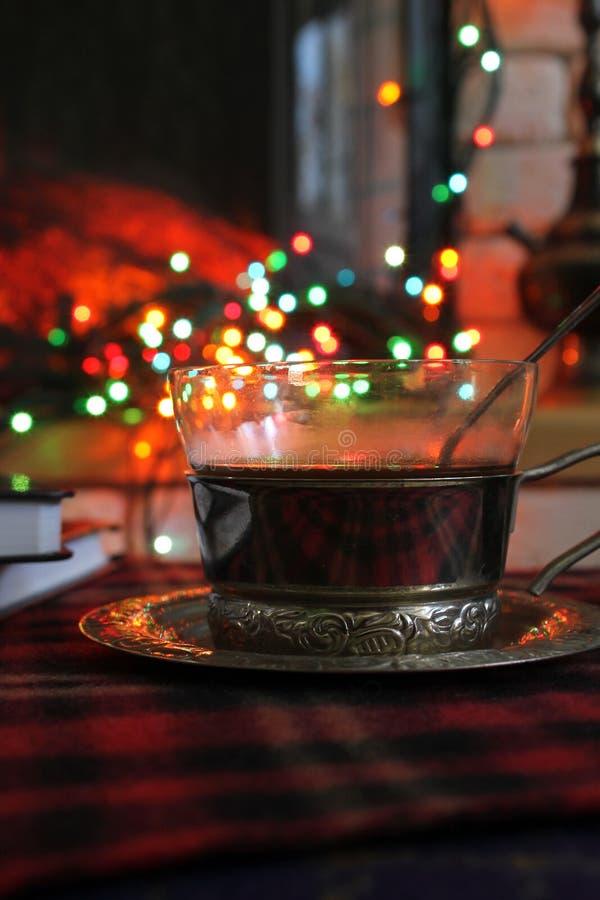 Transparente Tasse Tee in einem Stahlbecherhalter auf dem Hintergrund eines brennenden Kamins und der Weihnachtsgirlande stockbilder