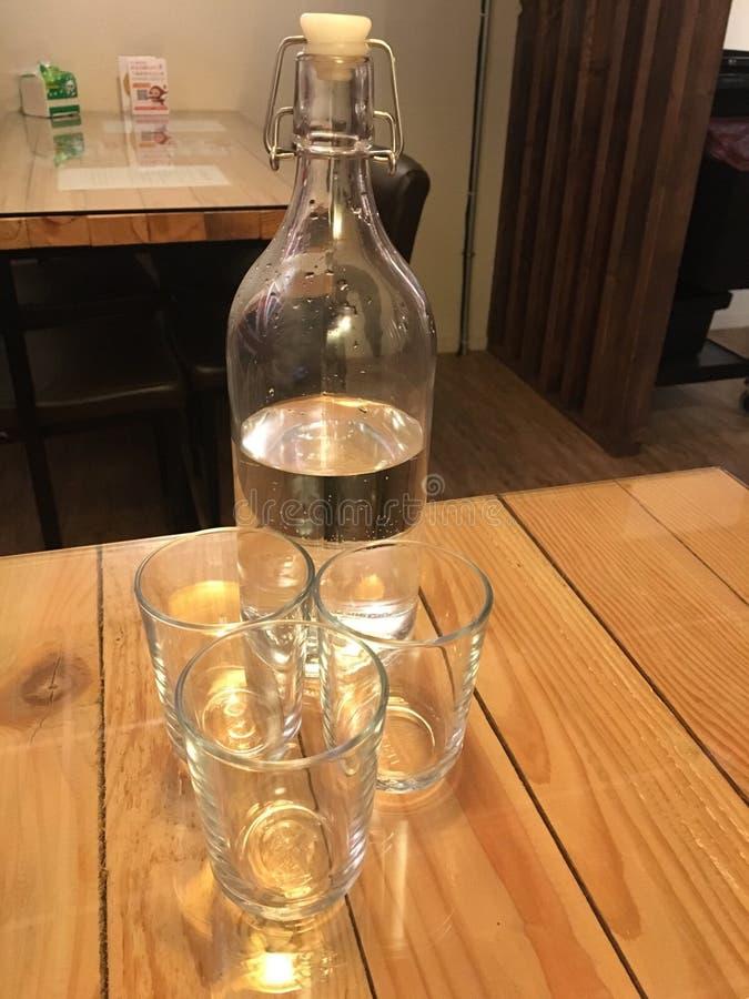 Transparente Wasserflasche und drei transparente Schalen lizenzfreie stockfotos