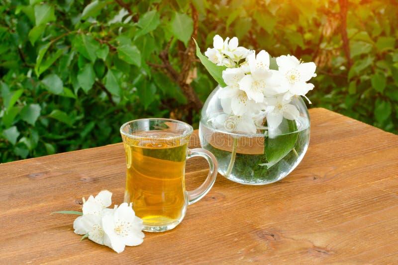 Transparenter Becher Tee und ein Vase mit Jasmin Grüns auf dem Ba lizenzfreie stockfotos