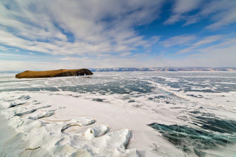 Transparentes Eis mit Sprüngen auf dem Baikalsee nahe Shamanka-Klippe Winter Baikal See, Russland stockbild