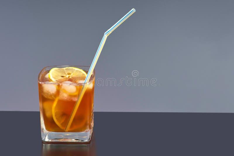Transparentes Glas mit kaltem Tee-, Eis-, Zitronen- und Cocktailröhrchen lizenzfreie stockfotos
