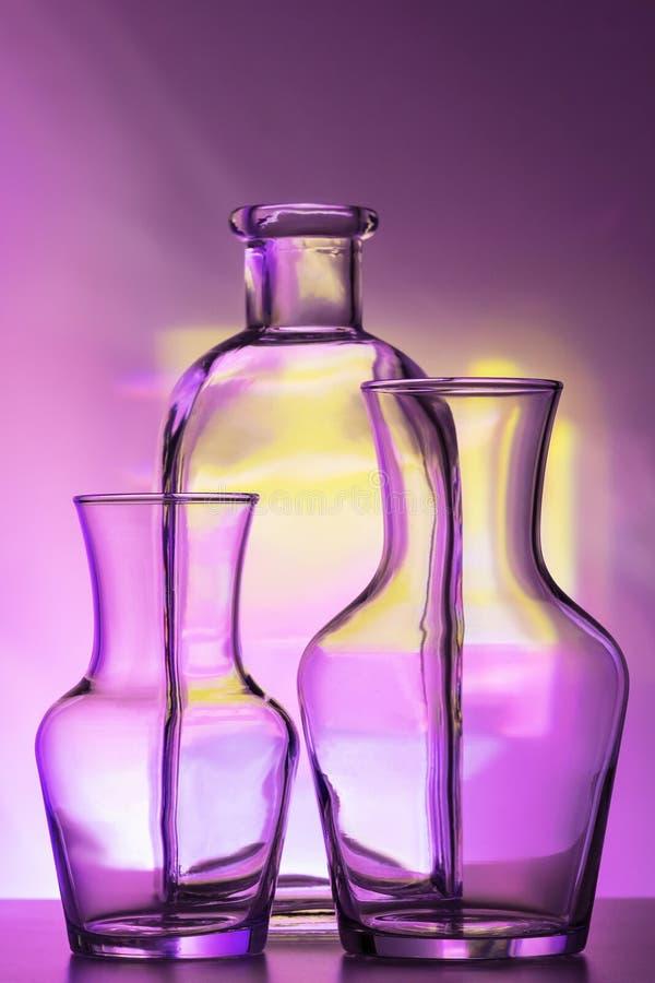 Transparentes GlasGeschirr - Flaschen verschiedene Größen, drei Stücke auf einem schönen mehrfarbigen, ein gelb, lila und stockfotografie