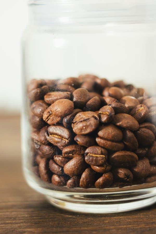Transparentes Glaskaffeeglas füllte mit Bohnen des Kaffees über dem dunklen Holztisch stockfoto