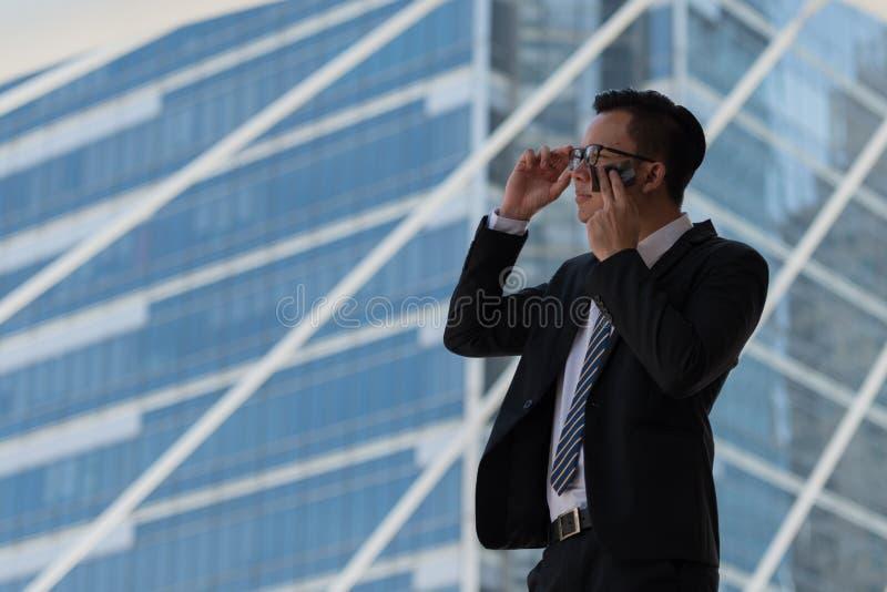 Transpiração asiática nova do homem de negócios devido ao clima quente Ele que limpa t imagens de stock