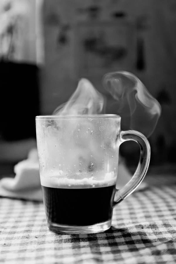 Transpiration avec la tasse de vapeur de café sur une table noire et blanche images stock