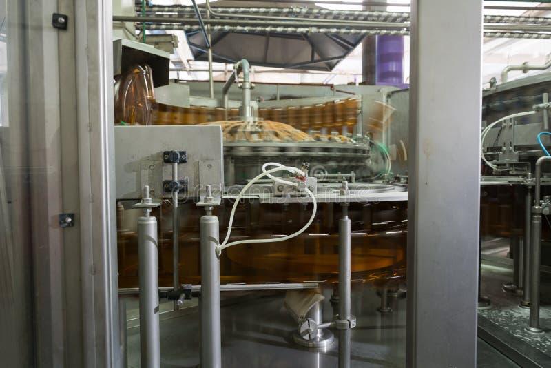 Transportören för fyllande HUSDJURflaskor som lokaliseras på bryggeriet arkivbild