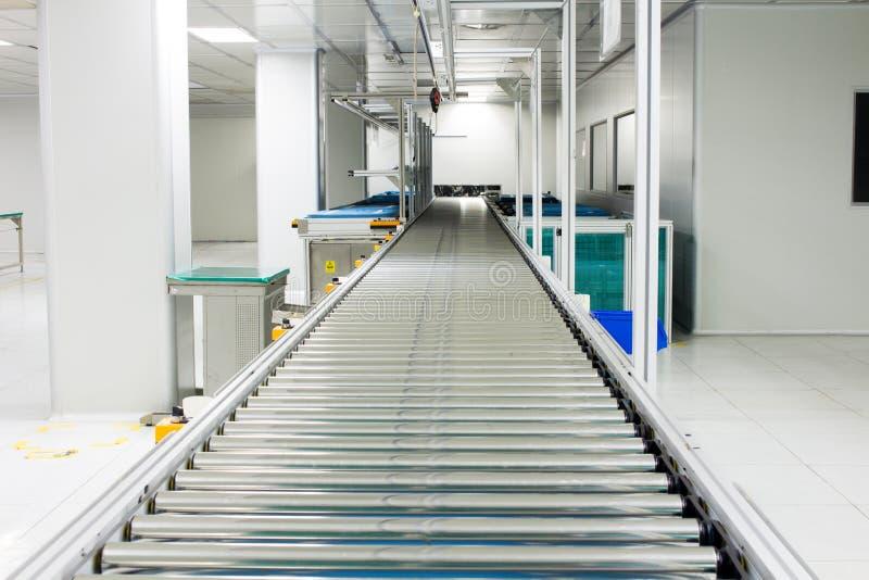Transportörkedjan och transportband på produktionslinjeaktivering i område för rent rum royaltyfri fotografi
