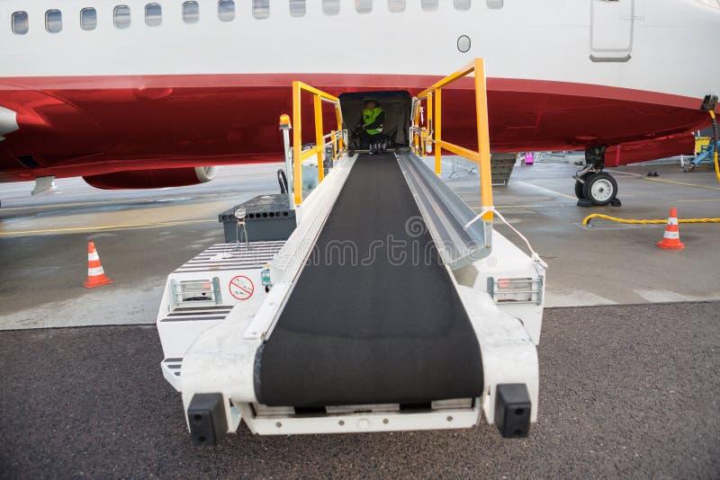 Transportörlastbil som fästas till flygplanet på flygplatslandningsbana royaltyfria foton