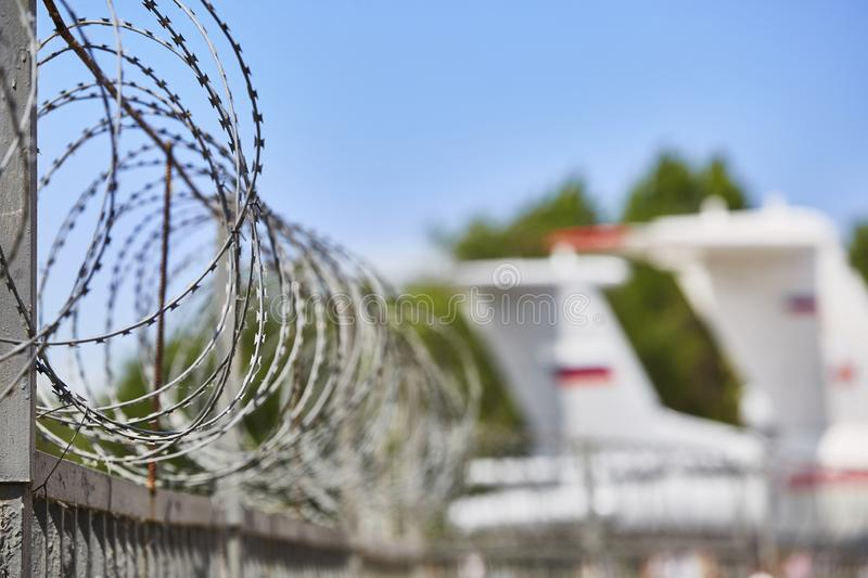 Transport aircraft stand at the airport fenced with barbed wire. Selective focus on the barbed wire fence.  royalty free stock image