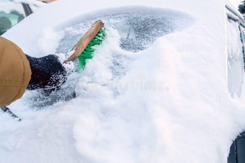 Transport bombardé par tempête de neige l'homme nettoie le pare-brise photo stock