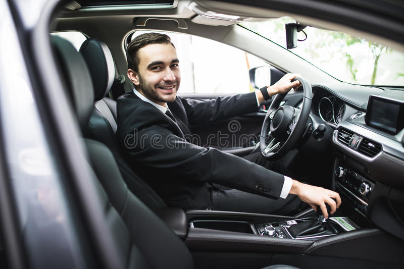 Transport, business trip, destination and people concept - close up of young man in suit driving car look at camera royalty free stock images