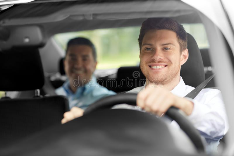 Male taxi driver driving car with passenger. Transport, people and taxi concept - happy smiling male driver driving car with passenger stock images