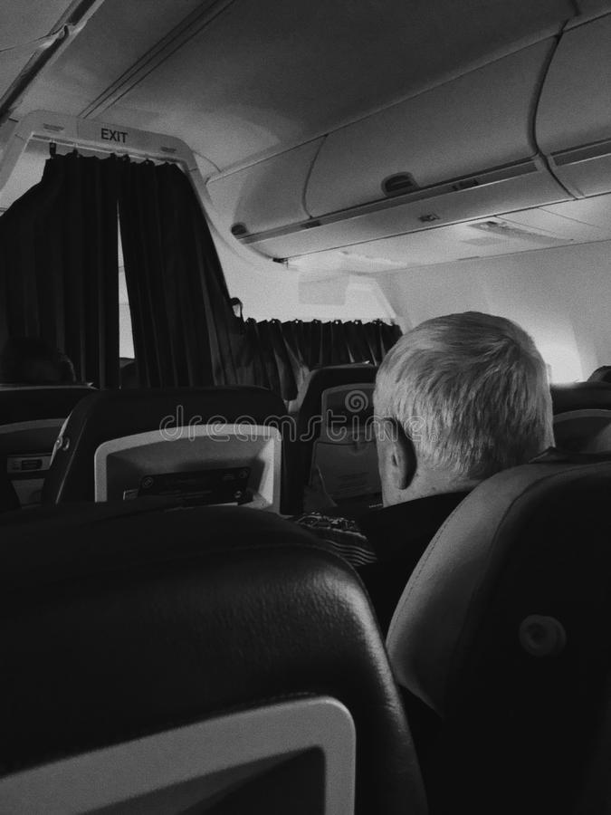 Respectable old man in a plane. Transport, tourism, trip and people concept - gray haired senior man sitting in airplane stock photography