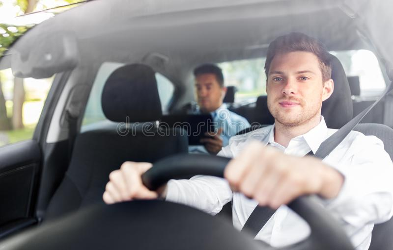 Male driver driving car with passenger stock images