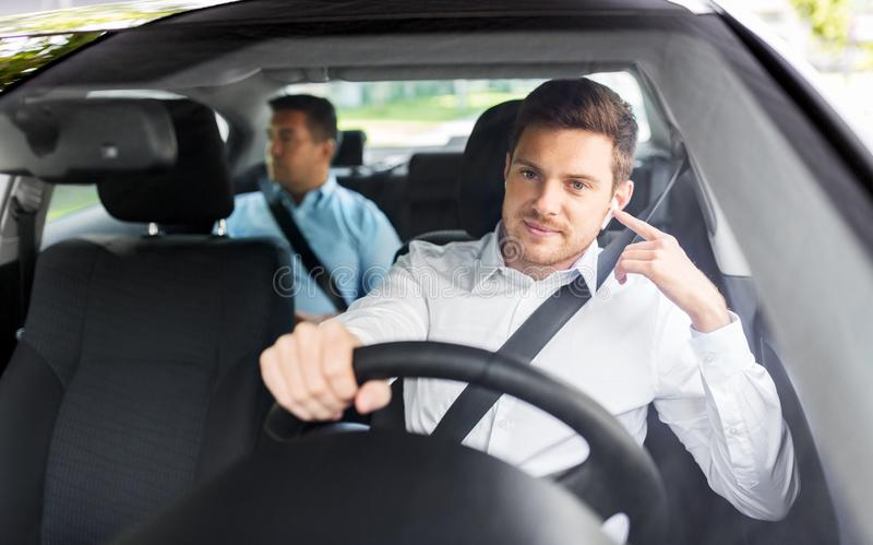 Male driver with wireless earphones driving car. Transport, vehicle and people concept - male driver with wireless earphones or hands free device driving car stock images