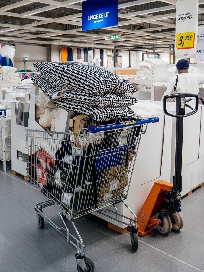 Transportador do carrinho de compras completamente com mercadoria em IKEA fotos de stock