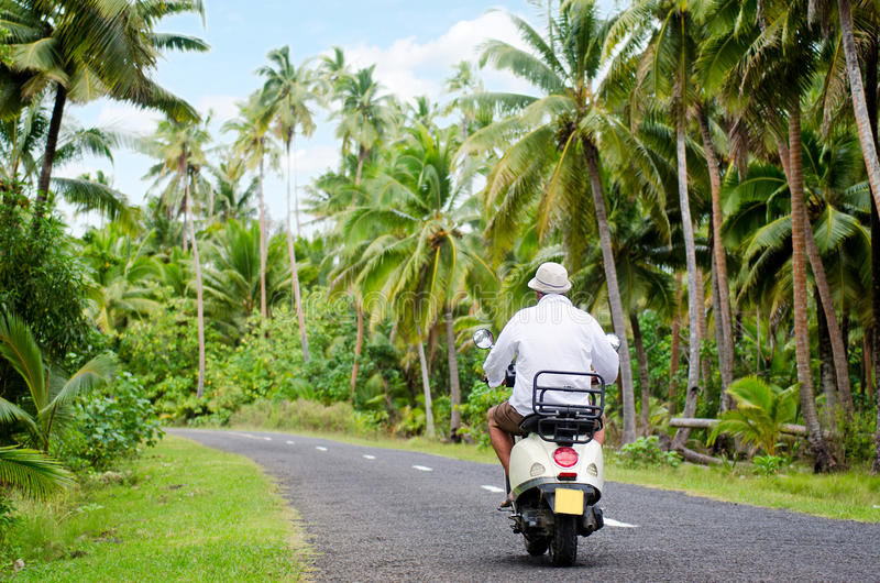 Transportation in Aitutaki Cook Islands. AITUTAKI - SEP 20:Tourist man drives hired motorbike on Sep 20 2013.It's one of the must popular activity in the Island royalty free stock photography